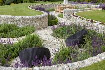 Sunken garden, wavy flint stone walls around crazy paving patio with chairs and Salvia verticillata 'Purple Rain'