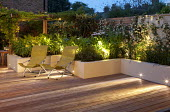 Deckchairs on terrace, raised beds with lighting, Trachelospermum jasminoides on fence
