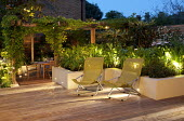 Contemporary urban garden with lighting, deckchairs, table and chairs under pergola