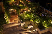 Overview of contemporary urban garden with lighting, deckchairs, pergola and raised beds