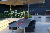 Table and chairs under umbrella on patio, Hydrangea arborescens 'Annabelle', lighting on steps, outdoor kitchen and grill