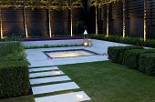 Stepping stone path across lawn to jacuzzi terrace, uplit pleached Pyrus calleryana 'Chanticleer' against black painted fence, lanterns and candles