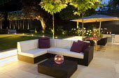 Outdoor furniture with cushions, table and chairs with umbrella, urban garden at night, Platanus x acerifolia, syn. Platanus x hispanica
