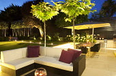 Platanus x acerifolia, syn. Platanus x hispanica, outdoor furniture with cushions on patio, table and chairs