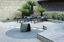 Courtyard with Dicksonia antarctica, sculpture by Dennis Fairweather, circular paving pattern, sun loungers