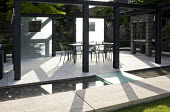 Metal table and chairs on patio enclosed by frosted glass screens and surrounded by shallow rill, outdoor grill