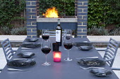 Table set for evening barbecue with wine and candles, built-in barbecue, outdoor kitchen