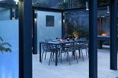 Metal table and chairs on enclosed patio, set for evening barbecue with wine and candles