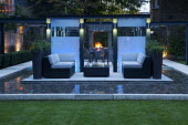 Contemporary outdoor Rattan furniture with cushions on 'floating' terrace surrounded by shallow pebble pool, built-in barbecue