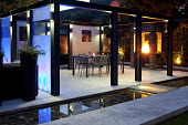 Table and chairs on contemporary enclosed patio, uplit screens, built-in barbecue