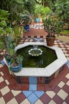 Geometric tile pattern around raised octagonal fish pond in Moroccan-inspired courtyard garden