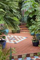 Geometric tile pattern in Moroccan-inspired courtyard garden, Paulownia tomentosa