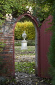 Doorway in brick wall leading from secret garden, urn ornament, roses