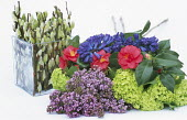 Ingredients for spring flower arrangement with camellias, syringa and hyacinths, pussy willow in glass vase