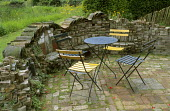 Paved seating area with walls made from reclaimed bricks and tiles, metal table and chairs