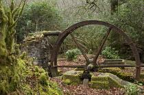 Old metal water wheel in woodland