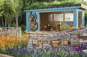 Office with living green roof created from recycled cargo shipping container, dry-stone walls with wildlife habitats planted with sempervivums, Geum 'Prinses Juliana'