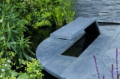 Circular slate terrace with bench surrounded by water