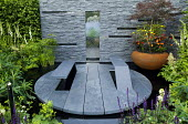 Circular slate terrace with projecting built-in benches, slate wall with solar panels and water fountain