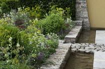 Stone walls edging border, rill, Centranthus ruber 'Albus'
