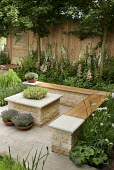 Built-in timber benches around stone table, thyme in containers, foxgloves and rodgersias