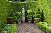 Enclosed courtyard garden 'room' with brick paving, female statue on plinth, clipped yew hedges, spiral topiary in containers