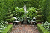 Enclosed courtyard garden 'room' with brick paving, female statue on plinth, clipped yew hedges, spiral box topiary in containers, white metal chairs, Brugmansia x candida