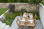 Table and chairs set for breakfast in sunken garden, dry-stone wall