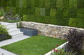 Water trough and fountains in dry-stone wall in sunken garden, living green heather wall with chequerboard pattern, square lawn