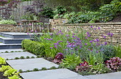 Terraced garden, dry-stone wall, table and chairs on patio, Erysimum 'Bowles' Mauve', Primula vialii
