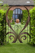 Contemporary copper gate by Steve Myburgh framing house window