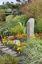 Standing stone in border, gazania, irises, Phormium tenax 'Variegatum', Salix viminalis