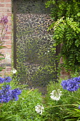 Ornate bronze gate by Jamie Fobert in brick wall, Agapanthus Headbourne hybrids, Wisteria sinensis