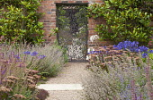Ornate bronze gate by Jamie Fobert in brick wall flanked by Magnolia grandiflora, Hylotelephium 'Matrona' syn. sedum, agapanthus, nepeta