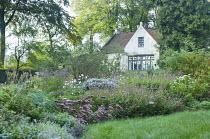 View across perennial border to white cottage