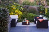 Contemporary outdoor Rattan chairs and sofa with cushions on patio, uplit Tetrapanax papyrifer, Miscanthus sinensis 'Ferner Osten', black basalt stone paving