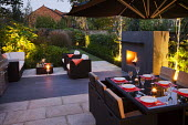 Contemporary outdoor Rattan table and chairs on patio by house, set for alfresco dining, outdoor fireplace, black basalt stone paving