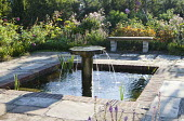 Water fountain in formal square pond with brick edging, flagstone paving, stone bench