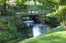 Weir on river beneath wooden bridge