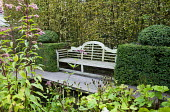 Wooden Lutyens bench flanked by topiary overlooking pond