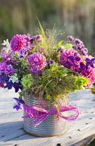 Cut stems of dahlia, Moluccella laevis, Verbena bonariensis and Salvia viridis in recycled tin can vase, ribbon, floral arrangement