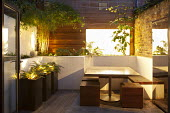 View from inside house to tiny urban courtyard, table, wooden stools and built-in benches, tall containers with Polystichum polyblepharum, mirrored wall water fountain, garden 'room', Himalayacalamus...