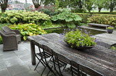 Rustic wooden table and chairs on patio overlooking formal pond, hosta, Hydrangea arborescens 'Annabelle', gunnera, eupatorium, bench