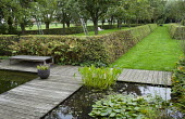Apple orchard in clipped hornbeam hedge enclosure, formal ponds, bench