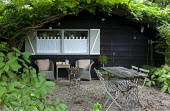 Rustic table and chairs under tree by shed