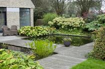 Chairs on terrace by house overlooking formal fish pond, decking bridge, Hydrangea arborescens 'Annabelle', hosta, gunnera, eupatorium, Alchemilla mollis, Miscanthus sinensis 'Zebrinus',