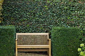 Wooden bench between clipped box cubes, ivy screen