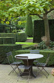 Table and chairs on brick patio, formal garden with clipped yew hedges