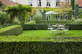 Metal table and chairs on lawn in clipped hedge enclosure