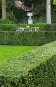 Clipped box hedges forming garden 'rooms', table and chairs, urn